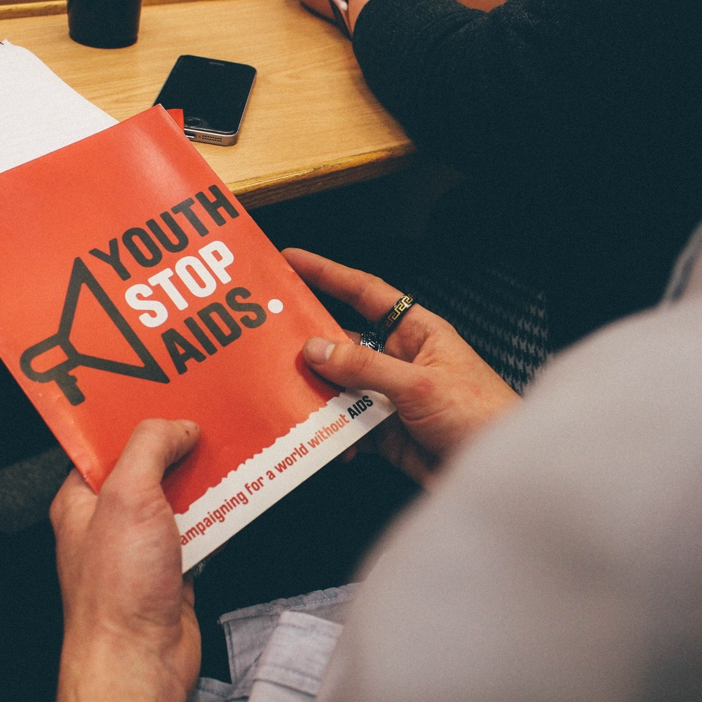 A person reading a brochure about Youth Stop Aids at a desk